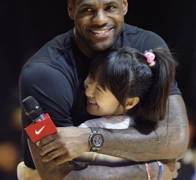 NBA basketball player James of Miami Heat hugs Chinese fan during promotional event at gymnasium in Beijing
