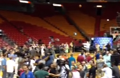 LeBron casually shoots a half-court jumper in the middle of swarm of reporters