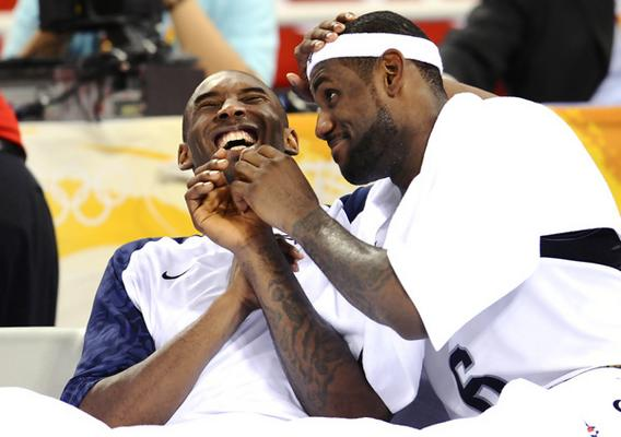 Kobe Bryant and Lebron James [USA]  have a laugh on the bench.